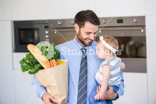 Businessman carrying vegetables and daughter