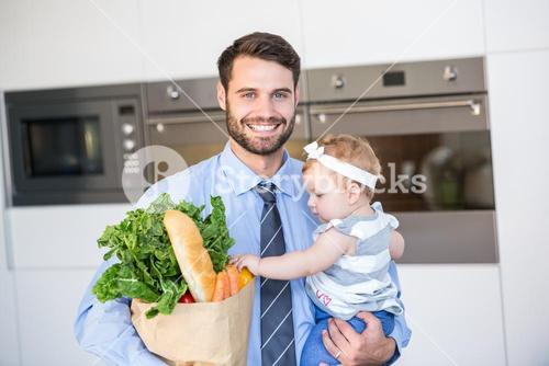 Happy businessman carrying vegetables and daughter