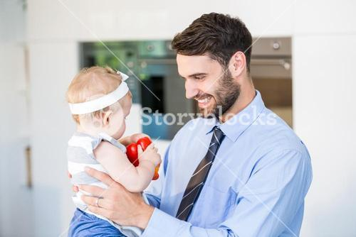 Happy businessman playing with daughter