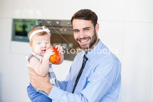 Portrait of happy businessman playing with daughter