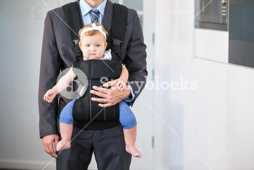 Businessman carrying cute daughter at home