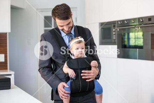 Businessman carrying daughter at home