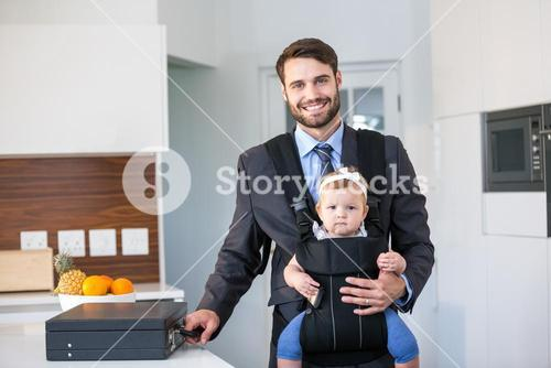Confident businessman carrying daughter by table