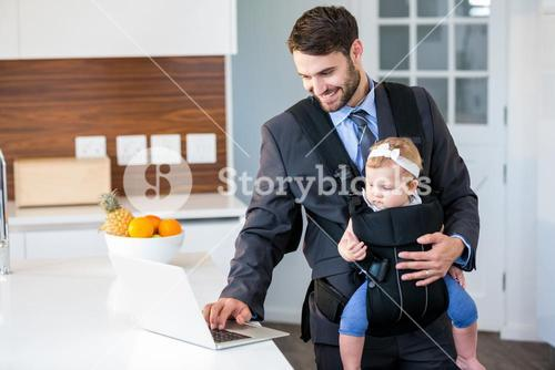Businessman using laptop while carrying baby girl