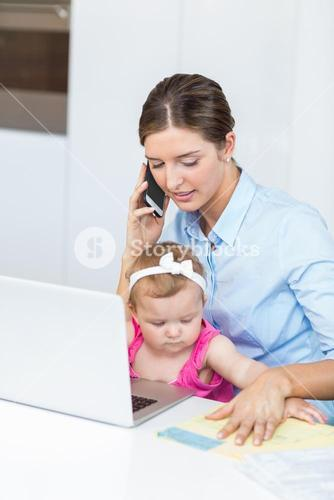 Woman talking on mobile phone sitting with baby girl