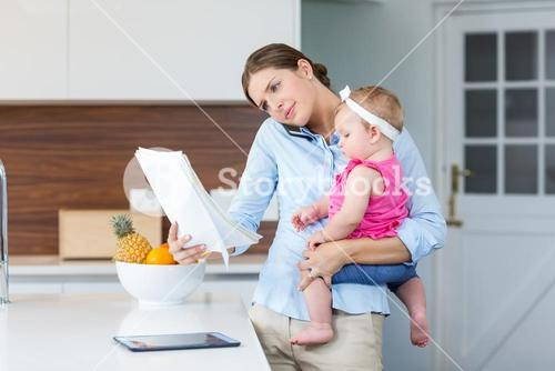 Woman reading documents while carrying baby girl