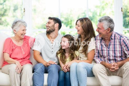 Family laughing while sitting on sofa