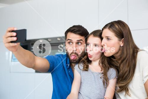 Family sticking out tongue while clicking selfie