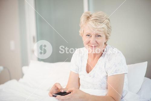 Senior woman using phone in bed