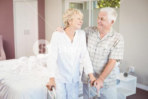 Senior smiling couple with walker