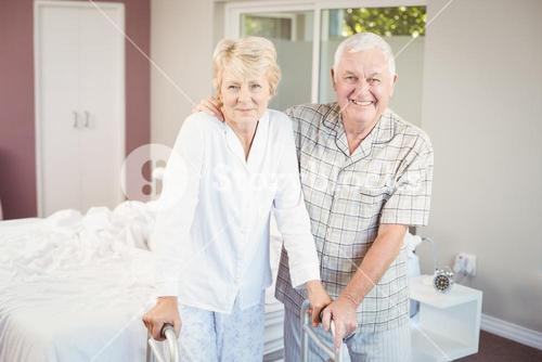 Portrait of senior smiling couple with walker