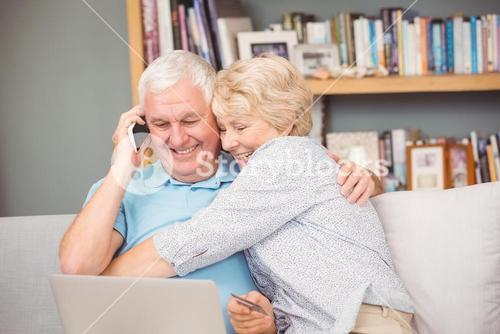 Excited senior woman hugging her husband while using laptop