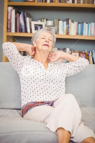 Senior woman suffering from neck pain on sofa
