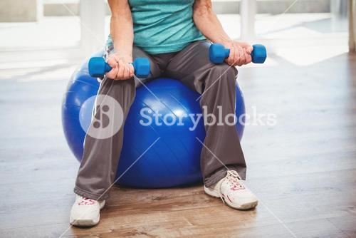 Low section of woman holding dumbbell