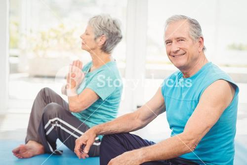 Portrait of smiling man sitting beside wife