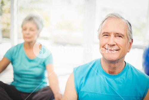 Portrait of senior man smiling with wife meditating