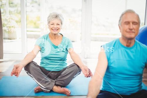 Portrait of smiling senior woman with husband meditating