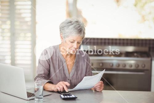 Senior woman using calculator while holding document
