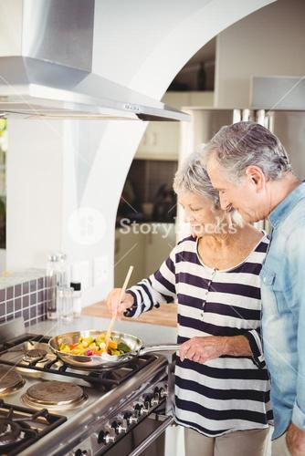 Senior couple cooking food in kitchen