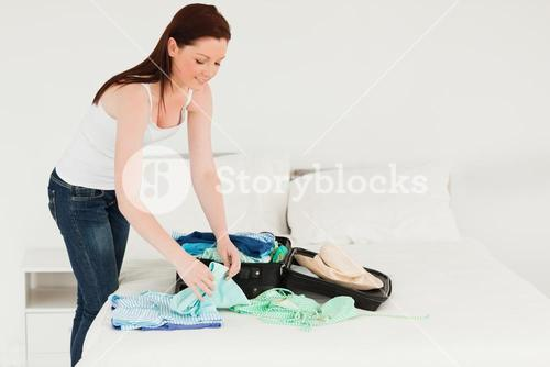 Beautiful woman packing her suitcase