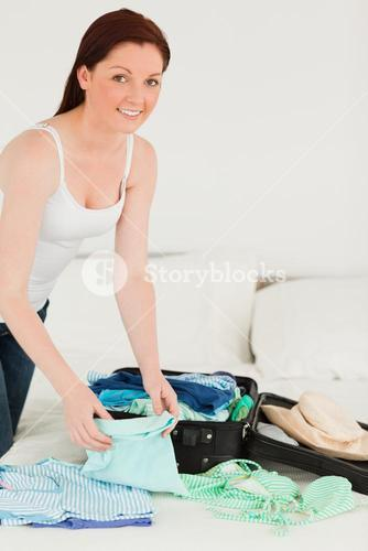 Good looking woman packing her suitcase
