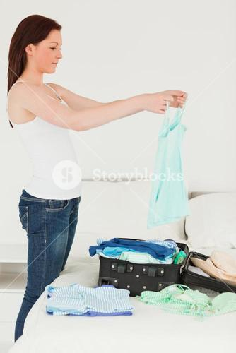 Pretty woman packing her suitcase