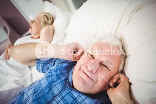 Portrait of man covering ears from snoring wife