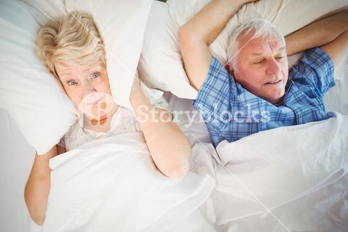 Portrait of woman covering ears from snoring husband