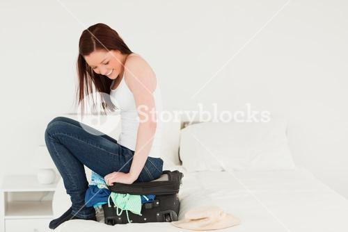 Good looking woman sitting on her suitcase