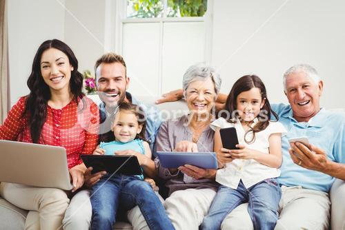 Portrait of happy family holding technologies at home