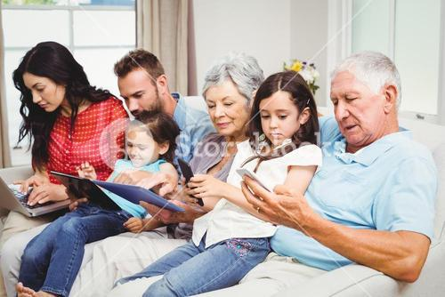 Family using technologies while sitting on sofa