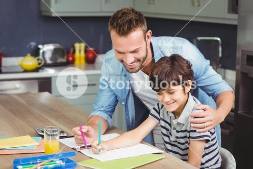 Father assisting boy in solving maths