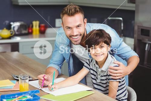 Portrait of father assisting boy in solving maths
