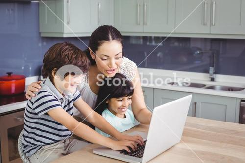 Smiling mother and children working on laptop