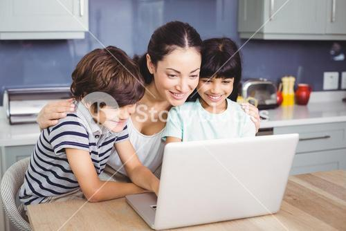 Happy mother and children working on laptop