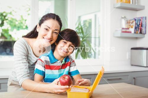 Portrait of smiling mother and son with lunch box