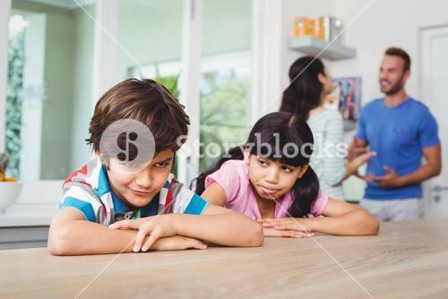 Children making faces while sitting at table