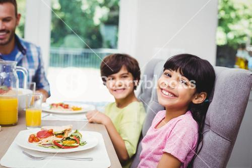 Smiling children sitting at dining table