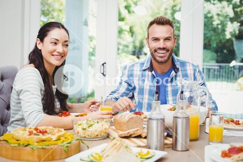 Smiling couple sitting at dining table