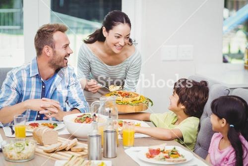 Smiling mother serving food to children