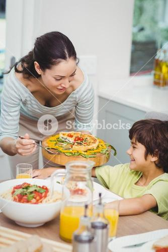 Mother serving food to son