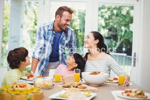 Smiling family discussing at dining table