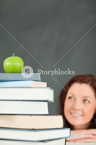 Young student with a stack of books and an apple