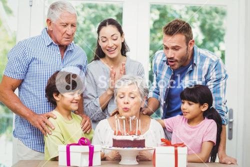 Granny blowing birthday candles with family