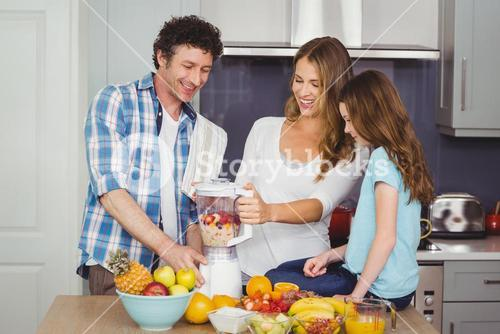 Parents and daughter preparing fruit juice
