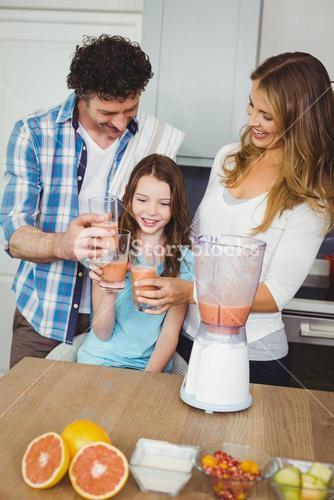 Smiling family toasting fruit juice