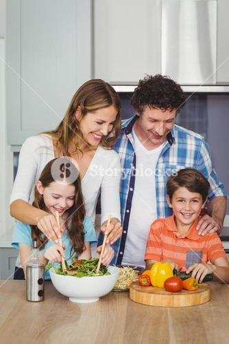 Happy family standing by table in kitchen