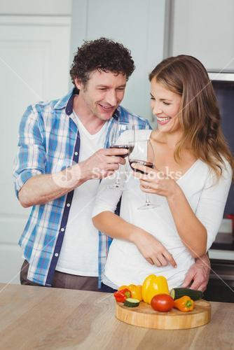Young couple toasting wine in kitchen