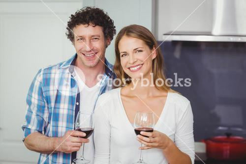 Portrait of young couple holding wineglasses in kitchen