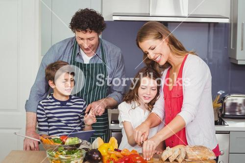 Happy parents with son and daughter in kitchen